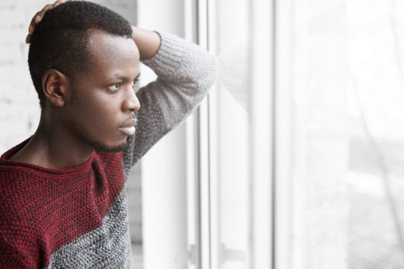 Sad dark-skinned male in casual sweater touching his head and staring through window glass with unhappy and depressed look, suffering from creative frustration, can't find inspiration at new job